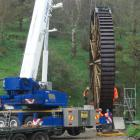 The newly-restored historic Phoenix Mill water wheel is lifted into place at its original site in...