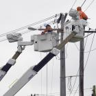 Downer linesmen work on pole replacement in Tomkins St, Green Island, yesterday. Since January...