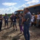 Eric Watson (front centre, in shorts and dark blue top) listens during a farm visit between...