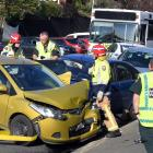 Emergency services prepare to pull a Mazda Demio out of the way so a woman (obscured) trapped...
