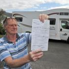 Macandrew Bay retiree Neil Morris holds a freedom camping ticket he received recently while...