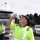 Truck driver Graham Veitch enjoys water provided by NZ Transport Agency transport officer Greg...