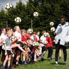 Tottenham Hotspur international development coach Anton Blackwood shows the pupils of Fairfield...