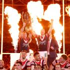 Roosters players celebrate with the trophy after beating the Melbourne Storm in the 2018 NRL...
