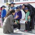 The Duchess of Sussex attempting to coax a smile from 5-year-old Joe Young while meeting with...