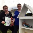 Tracey Leishman and her son Daemon (11) fix a vandalised community fruit and vegetable stand on...