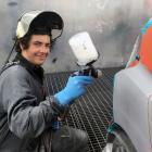 World Skills New Zealand national competition gold medal winner Callum Dodds paints a car in a...