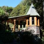 Ian Melvin's art studio, complete with turret, is nestled in regenerating native bush that the...