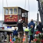 Onlookers take photographs as the Roslyn No95 cable car is lifted into the Dunedin Heritage Light...