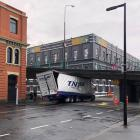 A TNL Freighting truck is stuck under the Jetty St overpass at the intersection with Vogel St....
