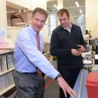 United States ambassador Scott Brown (left) discusses an Antarctic core sediment sample with...