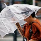 A woman struggles against strong wind and rain as Typhoon Jongdari approaches Japan's mainland....