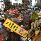 Proctor Auctions owner Ronald Proctor holds an advertising sign, which will be among 700 lots...