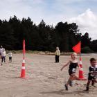 The children running at high speed in the 2km beach run.