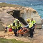 Rescuers carry a 25-year-old woman in a stokes basket after she slipped and fell  at Tunnel Beach...