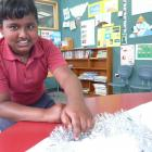Clutha Valley School pupil Janindu Mallawaarachchi (11) staples tinsel to a sheet to be used for...