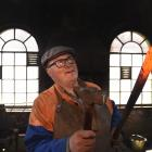 Builder and engineer Peter Mason holds a steel bar with a tip  heated to more than 1200degC after...