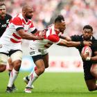Waisake Naholo fends off two Brave Blossoms in the All Blacks Japan test in Tokyo. Photo: Getty...