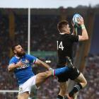 All Black wing Jordie Barrett collects the high ball ahead of Italy fullback Jayden Hayward to...