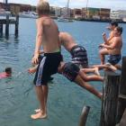 Children jump off the wharf at a boat ramp in Bluff in January. Photo: Sharon Reece
