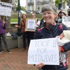 Dunedin midwife Louise Bell with 3-week-old Thomas Sawyer, during the Midwifery Employee...