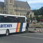 A Ritchies bus driver inspects the damage after his bus struck a railway crossing pole in lower...