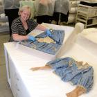Toitu Otago Settlers Museum registrar Claire Orbell examines an Edwardian blue silk wedding dress...