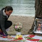 Katie Stafford places a candle at the memorial for Grace Millane in Queenstown. Photo: Mountain...