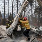 Firefighters move debris while recovering human remains from a trailer home destroyed by the Camp...