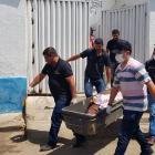 Forensic workers carry a container with a dead body after a shootout between police and bank...