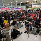 Passengers wait in the South Terminal building at Gatwick Airport after drones flying over the...