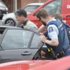 Police arrest a man after he evaded police at a checkpoint in Dunedin yesterday afternoon. Photo:...