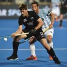 Black Sticks striker Marcus Child controls the ball as Argentina defender Pedro Ibarra looks on...