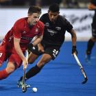 England forward Liam Ansell (left) is shadowed by New Zealand midfielder Arun Panchia during...