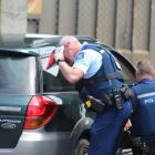 Police investigate the car which was abandoned at the former Invercargill Railway Station on...
