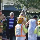 Firefighters help a woman to a waiting ambulance after a fire at Dunedin home yesterday afternoon...