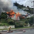 Fire crews work to put out a fire that destroyed a Reed St, Oamaru, home and set alight a neighbouring property yesterday. Photo: Logan Harris