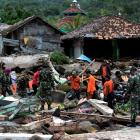 Rescue team members search for victims among debris after a tsunami hit at Rajabasa district in...