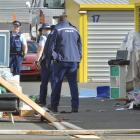 Police inspect items strewn across the driveway of a Dunedin storage facility belonging to a man...