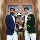 Captains Virat Kohli and Tim Paine hold the trophy India and Australia will play for in their...
