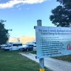 A line-up of camping vehicles begins near a sign outlining the rules of the Burton Creek camping...