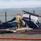 Clutha Valley firefighter Leonard Cunningham damps down the embers of a dairy farm shed after a...