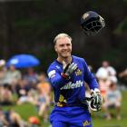 Otago wicketkeeper Ben Cox tosses his helmet to a player during the Super Smash game against...