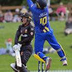 Wellington wicketkeeper Tom Blundell hits the ball while Otago wicketkeeper Ben Cox jumps in the...