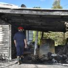 Fire and Emergency New Zealand investigator Mark Bredenbeck examines a home in Beechworth St...