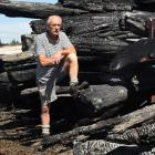 Surveying the charred remains of timber consumed in the Burnside fire is Valley Lumber owner...