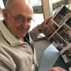 """Dennis Bird looks over some of the many photos he took which helped earn him an on-tour """"Steven..."""