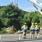A crane prepares to retrieve a gravel truck from the side of the Southern Motorway after it...