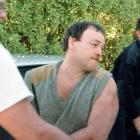 Arthur Taylor is escorted from the back of a police vehicle at the Tairua Police station in 1998...
