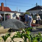 Telford staff take part in a working bee at the Balclutha Community Garden this morning. Photo:...